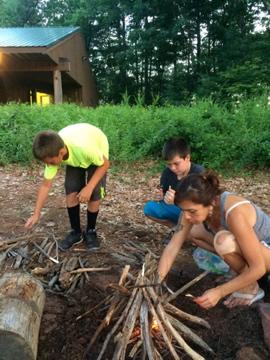 Starting a bonfire at camp